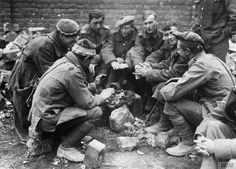 British prisoners warming their hands around a basket of hot coals in a temporary POW camp, march-April 1918.