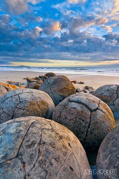 The Moeraki Boulders are unusually large and spherical boulders lying along a stretch of Koekohe Beach on the wave cut Otago coast of New Zealand between Moeraki and Hampden, and are located at 45°20′42.99″S 170°49′33.82″E. They occur scattered either as isolated or clusters of boulders within a stretch of beach where they have been protected in a scientific reserve.