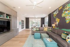 Blue and gray living room features an accent wall clad in a brown, yellow and green world map mural lined with a gray sectional and turquoise poufs atop a turquoise rug facing a full wall gray media cabinet fitted with a flatscreen TV.