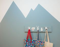 Create a wow factor by painting a kids' wall mural on one wall. We chose a striking mountain design and continued the theme with mountain animal coat hooks – kids will love hanging their clothes and bags on the animals' tails.