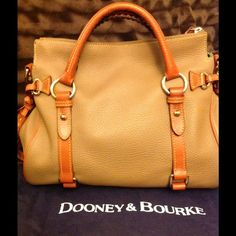 """Dooney & Bourke  ladies handbag top zip to the strap clips adds a luxe note to Dooney & Bourke's sublime leather satchel. Dooney and Bourke bag Leather Double handles with 8"""" drop; detachable, adjustable strap with 19"""" drop Top zip closure Gold-tone hardware throughout; double buckle detail and logo patch at front; fringe tassel at sides Interior features two-tone lining, zip pocket, key keeper hook and 2 open pockets, 1 with snap 13"""" W x 8"""" H x 5-3/4"""" D new no tags Dooney & Bourke Bags"""