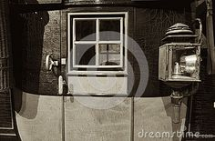 This is a vintage image of a turn of the century stage coach door with an oil lantern