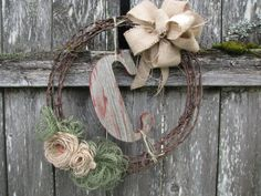 This Barb Wire wreath is made from 100+ year old barb wire from a farm in Oregon.     It is accented with burlap flowers in moss green and neutral