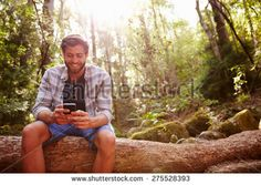 Man Sits On Tree Trunk In Forest Using Mobile Phone