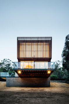 Maison en bois contemporaine sur le versant d'une colline en pleine forêt australienne, façade principale & porte à faux illuminée - Invermar House par Moloney Architects - Ballarat, Australie #construiretendance