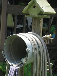 (Pb) OCD: Organize Clutter Delightfully ♥ on Pinterest | @djohnisee ~ PIC: DIY Wash Station ~  so simple & get's the water hose off the ground. Be creative & make it your own!  This example shows a galvanized pail screwed to a 2 x 4 that is in the ground with a bird house on the top & small wire baskets on backside. Roll the hose around the pail & use the inside as a place to store brushes, small garden tools, and a great place to hang a towel (when needed).