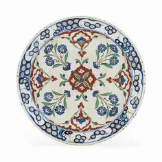 AN IZNIK POTTERY DISH   OTTOMAN TURKEY, CIRCA 1575   On short foot with sloping sides, the white ground painted in cobalt-blue, green and bole-red with black outlines with a central floral medallion surrounded by alternating floral bouquets and cusped medallions, the rim with stylised rock and wave design, the exterior with alternating floral sprays and cintamani circular motifs, repaired breaks  12 3/8in. (31.4cm.) diam.