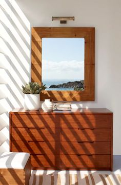 Ralph Lauren Home crushed bamboo mirror and cherry wood dresser catch the sun in a modern bedroom