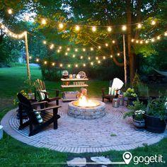 Los focos colgados hacen romántico y bello espacio al aire libre. Idea increíble para decorar un jardín.