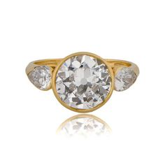 A stunning English Vintage Engagement Ring, bezel set in a beautiful yellow gold setting and shouldered by two pear-cut diamonds