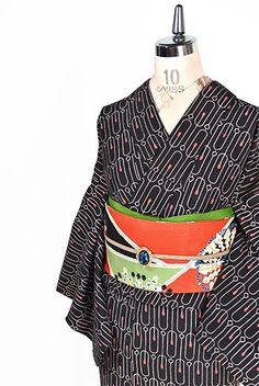 チャコールブラックに燭台のような曲線美しいモダンデザインが染め出された袷着物です。