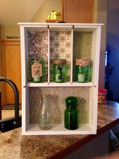 Repurposed drawer into a shelf. Wish I had a before picture.  Uses scrapbook paper in dividers.