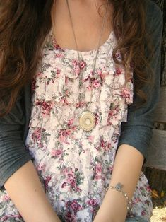 Ruffled printed shirt under a solid cardigan.  Sweet, feminine, and modest.