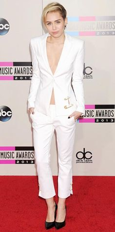 Look of the Day › November 25, 2013 WHAT SHE WORE At the 2013 AMAs, Miley Cyrus donned a slightly more conservative look, opting for a white Versus Versace suit with oversized gold safety pins along each side, and black pumps.