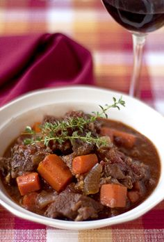 Sunday Beef Stew  2 tblsp. olive oil  8-12 garlic cloves, crushed  2 pounds chuck roast (trimmed and cut in cubes)  2 tsp. salt  ½ tsp. ground black pepper  1 cup red wine  8 carrots (peeled and cut in pieces)  2 medium onions, roughly chopped  ½ cup beef broth or stock  1 tblsp. tomato paste  1 14.5 oz can diced tomatoes  1 sprig fresh rosemary  several springs fresh thyme  1 bay leaf