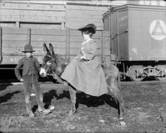 Colorado Springs, 1904. Singer and actress Anna Held is seated on a donkey next to a train in Colorado Springs (El Paso County), Colorado. A boy holds the reins.     Courtesy: Western History/Genealogy Department, Denver Public Library, Denver, Colorado (USA).