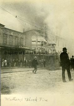"""This black and white photograph depicts a fire in the Mallard Block on Main Street in Laconia in 1904."""
