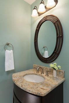 This small powder room feels fresh and clean due to the soothing ice-blue walls. The single vanity is topped with a neutral-colored granite, bringing an updated traditional look. The large, oval mirror works to open the space, making it feel larger.