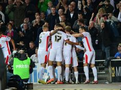 MK Dons players celebrate their second goal during the English League Cup second round football match between Milton Keynes Dons and Manchester United at Stadium MK in Milton Keynes, north of London, on August 26, 2014.