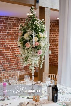 tall wedding table arrangement. Candelabrum decorated with flowers.