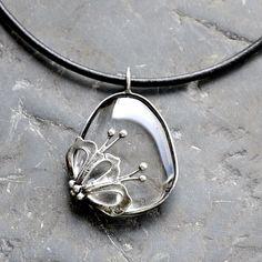 Kvítek  Šperk s křišťálembyl cínován, patinován a leštěn, ošetřen antioxidačním olejem. Zavěšen na černé kulaté kůži o délce 45 cm. Na přání mohu délku upravit. Velikost přívěsku je cca 5 x 3,5 cm.