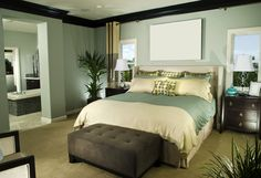 Wall Color - Small master bedroom in green, cream and brown color design. Brown suede bench at foot of bed opens up to reading chairs. Open doorway leads to en suite bathroom in same color scheme.