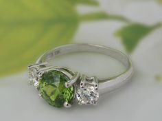 This ring features an extremely rare Demantoid garnet, 1.76ct, of Afghan origin from Kunar province. I personally cut this stone, using a modified Portuguese round cut (design by US Master Cutter John Bailey). Accenting this classic ring are 2 fine quality 0.24ct diamonds, G colour, VS1-2 clarity. Set in 3.41g of 18k white gold. Demantoid garnets in anything larger than a carat are a rarity. The stone exhibits superior fire and dispersion, not captured well in this photo. The garnet has fine…