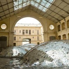 """Architect Clémence Eliard and artist Elise Morin created Waste Landscape, """"A Sea of Metallic Dunes"""". The installation, composed of 65,000 CD's were hand-sew together then laid over inflatable mounds to take over 1000 square meters in the Centquatre art space (Paris), and will will be on display from July 21st to September 10."""