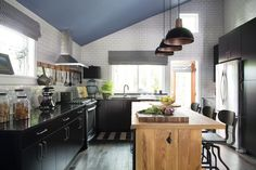 """Define a small kitchen space by running your """"backsplash"""" tile to the ceiling.  Love the classic colors in this kitchen."""