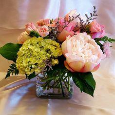 Centerpiece: Cube vase with fresh green mini hydrangeas, fresh pink spray roses, fresh pink roses (sweet unique), fresh white hydrangeas, fresh limonium, silk light pink peonies, fresh salal and fresh leather leaf.