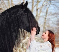 Friesian horse and red-haired woman in the snow