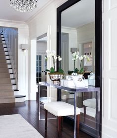 McGill Design Group gorgeous modern foyer design with espresso floor mirror, acrylic lucite console table, white bench, orchid, modern sconces with gray silk shades and crystal chandelier.