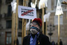 "A man stands next to a banner reading in Catalan: ""Freedom for Political Prisoners"" in support of Catalonia politicians who have been jailed on charges of sedition at Sant Jaume Square in Barcelona, Spain, Friday, Dec. 22, 2017. Elections in Cat"