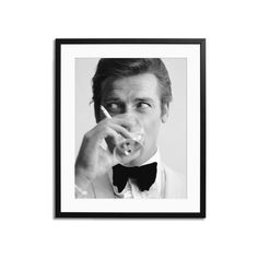 """""""A framed, limited-edition archival photo print of Roger Moore."""" English film star Roger Moore, well known for his roles as James Bond and the Saint, downs a martini. Each print is professionally framed and mounted to order using high quality wood frames. Top quality C-type and Giclée prints on Fuji Crystal Archive Paper. Photo by Peter Ruck. Printed and framed by Sonic Editions - a UK-based purveyor of archival music photography."""