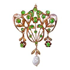 A polished rose and matte green 14K gold openwork floral pendant features twenty eight vibrant green Russian demantoid garnets and a beautiful baroque pearl.  This delicate Art Nouveau pendant was handcrafted in Moscow between 1908 and 1917.