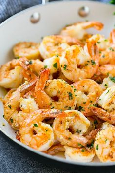 A pan of garlic butter shrimp in a savory sauce, finished off with chopped parsley. #seafoodrecipes