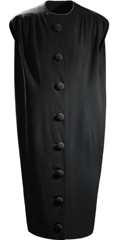 """Balenciaga """"sack dress"""", black wool crepe, 1957. This loose, comfortable dress contrasted with the fitted silhouette more common at the time. The """"barrel"""" line, so defined by the master, appeared in 1947. From that time on, Balenciaga experimented with the loose-fitting backs of his garments, creating the tunic dress in 1955 and the sack dress in 1957. He reinterpreted the female shape and eliminated the waist, creating silhouettes that were completely new in the history of fashion."""