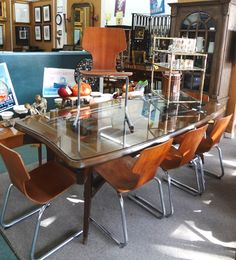 Large midcentury Argentine dining table with glass top. $1340 Set of 8 molded wood chairs. $188/each