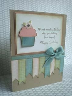 """by Michelle Andrews  'Create a Cupcake' stamp set, the Cupcake Builder punch, Crumb Cake cardstock for your card base, Baja Breeze, Blushing Bride and Whisper White cardstock. For the paper ribbon strips I used the 'Twitterpated' (DSP) from the Occasions Mini Catalog cut into various lengths at 1/2"""" wide. The bow is made from Baja Breeze Seam Binding attached with a glue dot. For the distressed look, I sponged all edges with Soft Suede"""