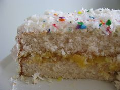 My favorite birthday cake: silver white cake, filled with tart lemon curd, covered in billows of white mountain frosting and topped with sweetened, shredded coconut. And sprinkles. Because it's a birthday.