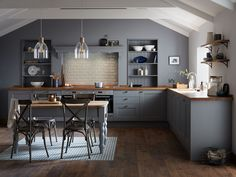 A dark grey Shaker style door with a wood grained detail. Create a uniquely stylish kitchen with colour-matched bespoke open shelving and an inlaid floor. Add interest with a solid Oak block worktop with a profiled finish and matching bespoke table top.  Fairford Slate Grey Kitchen by Howdens Joinery.