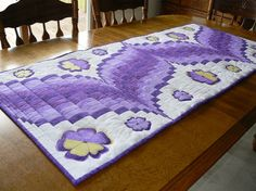 """This beautiful table runner is made of six different fabrics and done in the bargello-style. The quilt is strip-pieced and the pansies are appliqued on later. I used all cotton fabrics with a muslin backing and polyester batting. I also have four complementary placemats in the same fabrics. If you purchase both the runner and placemats you can save $10.00.  Not what you were looking for? Contact me and Ill work with you to make just the right item.  This table runner measures 60""""x25"""" Machine…"""