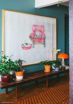 Banco de Sérgio Rodrigues decorado com vasinhos de plantas variadas.