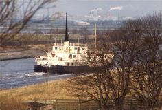 A boat on the Manchester Ship Canal as it runs between Flixton and Irlam