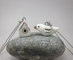 this looks like ceramic bird and birdhouse earrings. Super cute.
