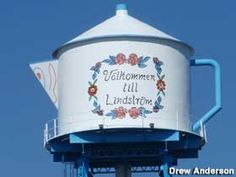 """""""Vilkommen lill Lindstrom,""""  A giant Coffee Pot Water Tower in downtown Lindstrom, Minnesota. Lindstrom was founded in the 1850s by Swedish settlers. The city's old water tower is in the shape of an appropriately decorated coffee pot. Standing above the """"America's Little Sweden"""" since 1902."""
