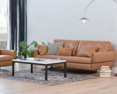 Distinguished style characterizes the Clementi sofa featuring a unique profile with detailed stitching, folded arms, tufted seating and prominent stainless steel legs.  Purchase online at SCANDIS.com
