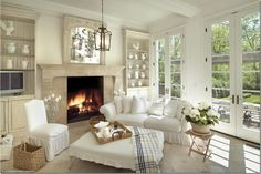 Love the built-ins, large fireplace, french doors and pretty furniture with all white slipcovers with ruffles and loose cushions.  So cozy!