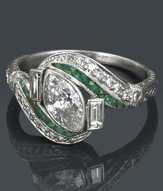 An Art Deco diamond and emerald ring, circa 1925. estimated total diamond weight: 1.00 carat; mounted in platinum.