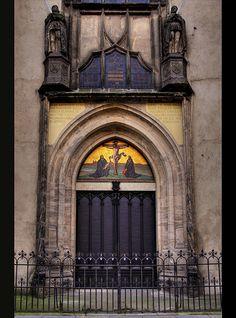 """De deur van de Slotkerk te Wittenberg waar Dr. M. Luther op 31 oktober 1517 de 95 Stellingen aansloeg. Afbeelding boven de ingang:De Gekruisigde Christus, Luther en Melanchton knielen aan de voet van de gekruisigde Heiland. """"De ware schat van de kerk is het Evangelie van de eer en genade van God"""" Stelling 62."""